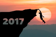silhouette-man-climbs-cliff-to-goal-setting-word-happy-new-year-sunset-background-80663885
